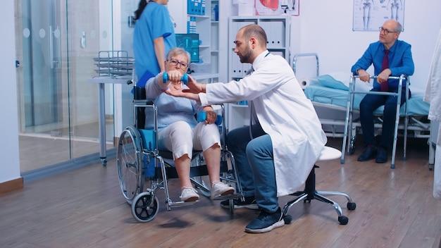 Arzt hilft alter behinderter frau im rollstuhl, muskelkraft in einer privaten erholungsklinik wiederzuerlangen. ungültige person, die hanteln zum trainieren verwendet. rehabilitationsklinik, arbeit mit gelähmten seni