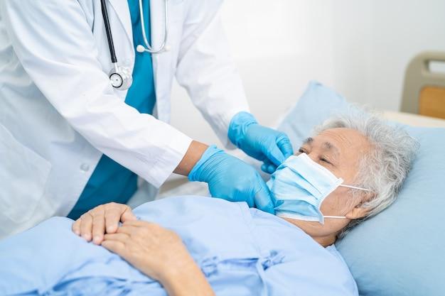 Arzt hilft asiatischer seniorin, die im krankenhaus eine gesichtsmaske trägt, um coronavirus zu schützen