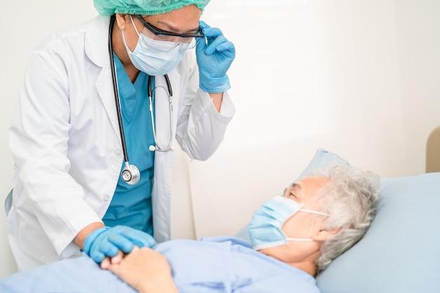 Arzt hilft asiatischer seniorin, die im krankenhaus eine maske trägt, um coronavirus zu schützen