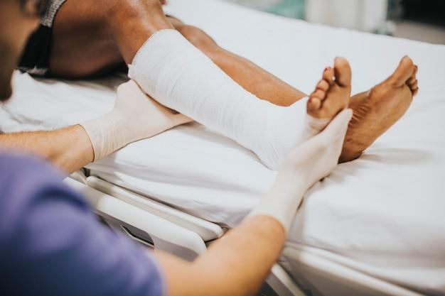Arzt hilft einem patienten mit einem gebrochenen bein