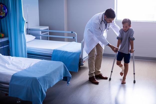Arzt hilft verletzten jungen, mit krücken zu gehen