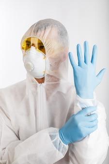 Arzt im anti-epidemie-anzug hält hände in handschuhen