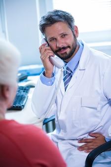 Arzt im gespräch auf festnetz-telefon in arztpraxis im krankenhaus