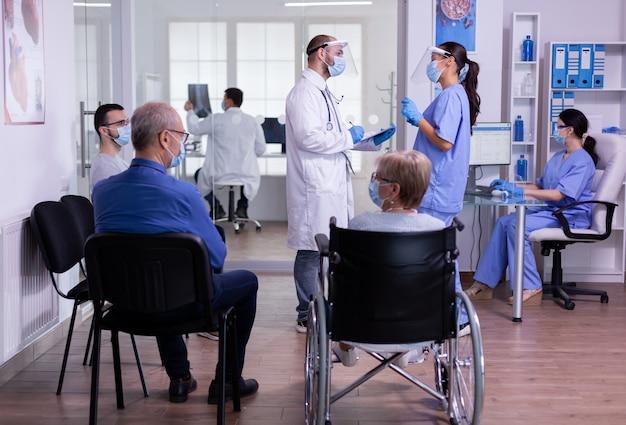 Arzt im gespräch mit einer krankenschwester mit gesichtsmasken, die eine zwischenablage halten und die behandlung erklären, die im wartezimmer der medizinischen klinik steht, bevor die patienten untersucht werden