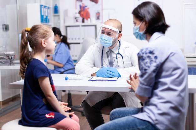 Arzt im gespräch mit kind während der beratung und ausbruch des coronavirus im krankenhausbüro mit gesichtsmaske. facharzt für kinderheilkunde, der beratungen zu gesundheitsdiensten anbietet