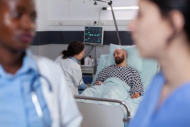 Arzt im gespräch mit medizinischem assistenten während der genesungsberatung, die in der krankenstation arbeitet