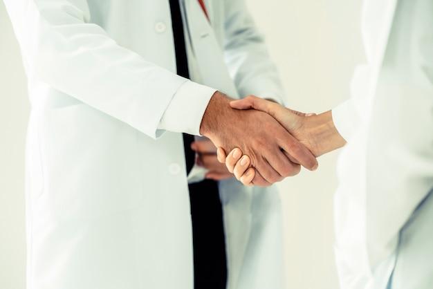 Arzt im krankenhaus schüttelt die hand mit einem anderen arzt