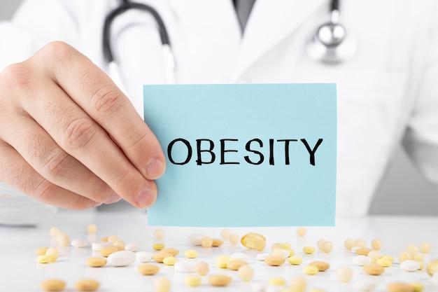 Arzt im schlafrock hält einen aufkleber mit text fettleibigkeit