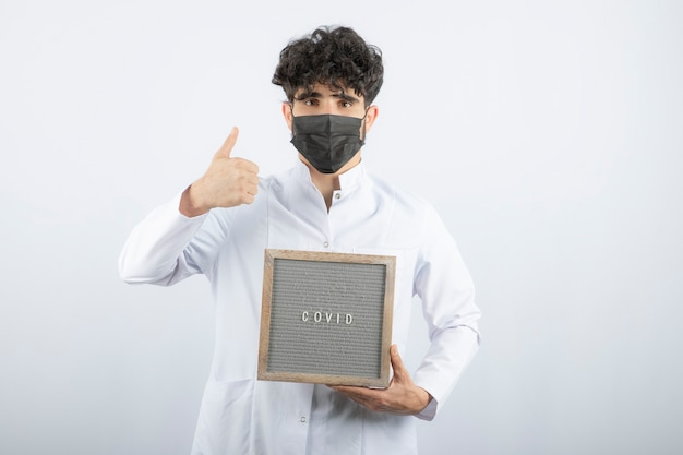 Arzt im weißen kittel mit stethoskop, das einen daumen zeigt, isoliert auf weiss.