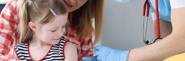 Arzt impft kleines mädchen in schulternahaufnahme