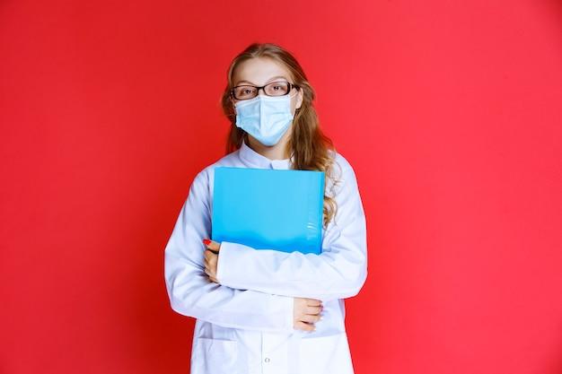 Arzt in blauer maske mit der geschichte des patienten.