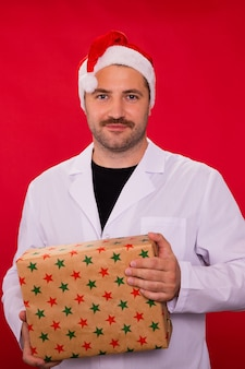 Arzt in der weihnachtsmannmütze hält weihnachtsgeschenkbox