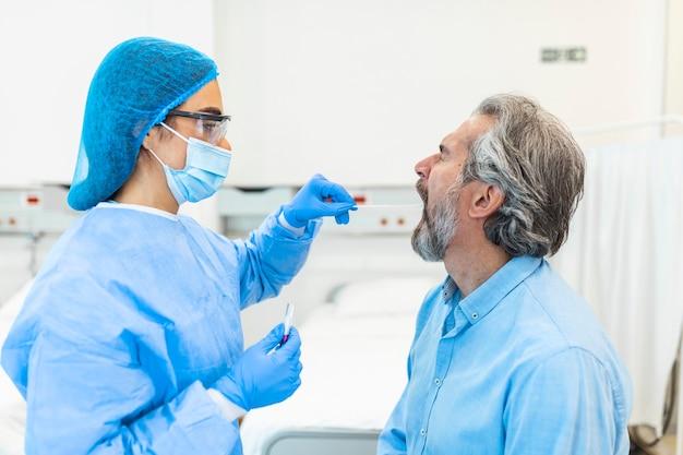 Arzt in einem schutzanzug, der einem patienten einen hals- und nasentupfer abnimmt, um auf eine mögliche coronavirus-infektion zu testen