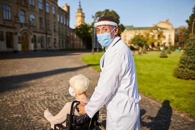 Arzt in einem weißen medizinischen kittel und gesichtsschutz, der unter der maske lächelt