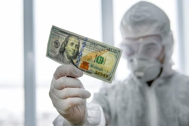 Arzt in einer schutzmaske und einem virenfesten anzug im krankenhaus zählt geld. zahlung an mitarbeiter im roten bereich. ein gefährlicher job mit geringem gehalt. auszeichnung für ärzte, die mit covid-patienten arbeiten