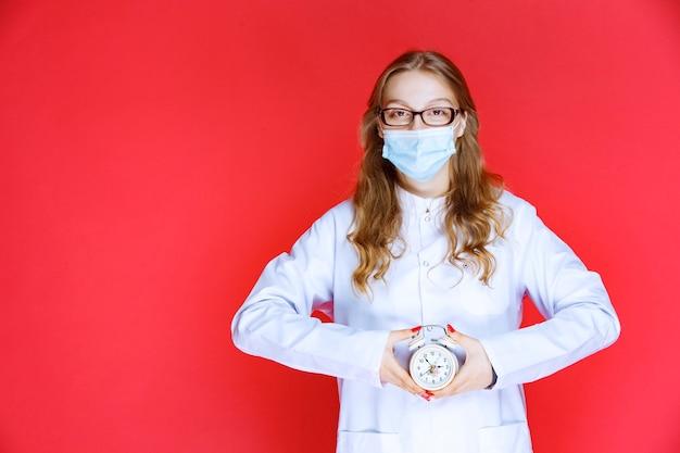Arzt in gesichtsmaske, der eine uhr zeigt, die die zeit für die einnahme von medikamenten bedeutet.