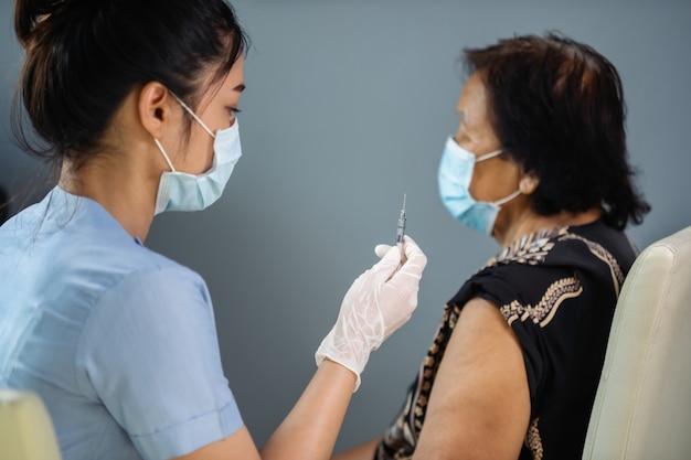 Arzt in handschuhen, die die spritze halten und dem älteren patienten in der medizinischen maske eine injektion machen