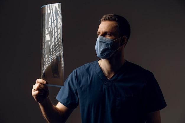 Arzt in medizinischer maske zum schutz des coronavirus covid-19 mit röntgenaufnahme eines kranken patienten. computertomographie.