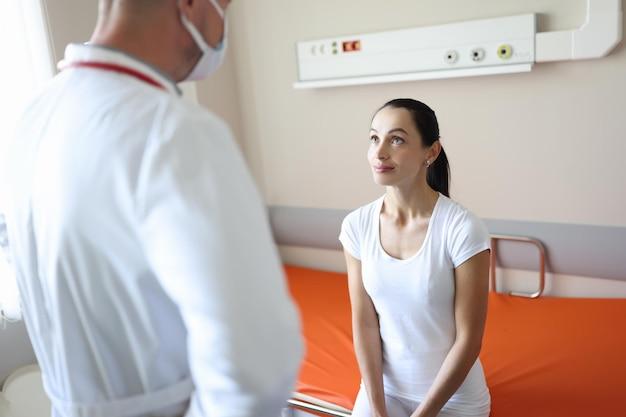 Arzt in medizinischer schutzmaske, der den patienten in der aufnahmeabteilung des krankenhauses untersucht