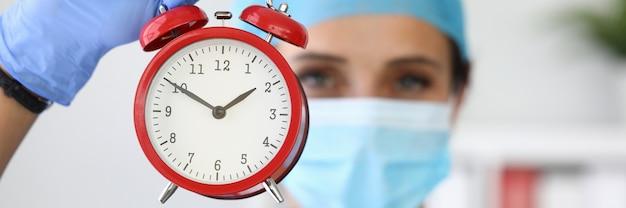 Arzt in medizinischer schutzmaske hält roten wecker in seinen händen. krankenversicherung und versicherungskonzept