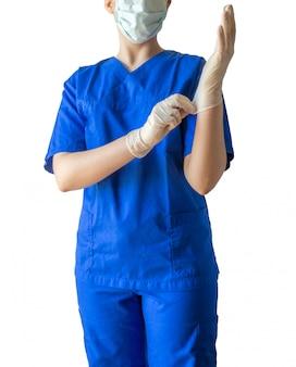 Arzt in medizinischer uniform und maske zieht medizinische handschuhe an und bereitet sich auf eine operation vor