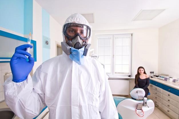 Arzt in schutzanzuguniform und maske hält injektionsspritze mit impfstoff.