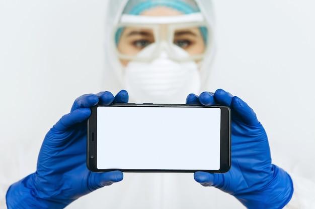 Arzt in schutzkleidung, atemschutzmaske, brille, handschuhe hält ein telefon. die ärzte drängten darauf, während der coronavirus-epidemie zu hause zu bleiben. covid-19