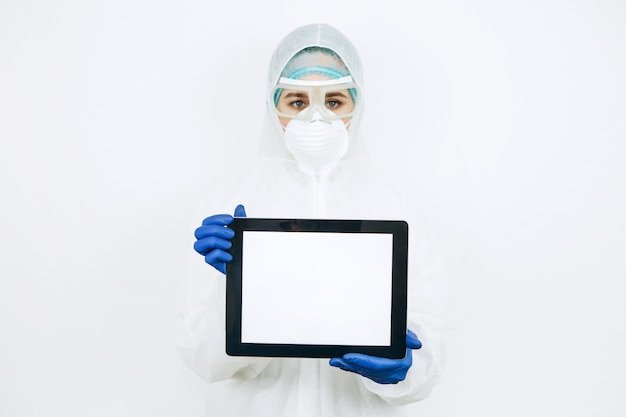 Arzt in schutzkleidung, atemschutzmaske, brille, handschuhe hält eine tablette. die ärzte drängten darauf, während der coronavirus-epidemie zu hause zu bleiben. covid-19