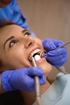Arzt in uniform, der die zähne der patientin in der zahnklinik überprüft.