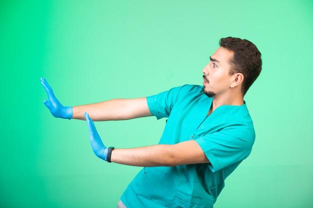 Arzt in uniform und handmaske verhindert sich auf grün.
