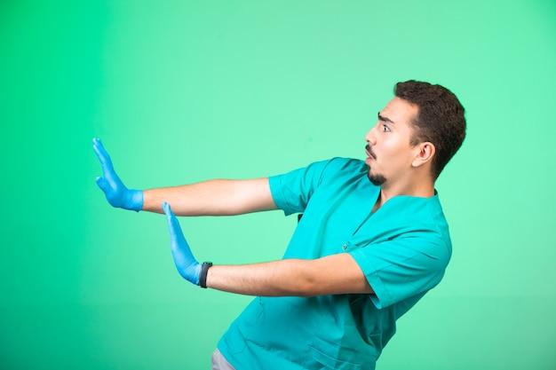 Arzt in uniform und handmaske verhindert sich.