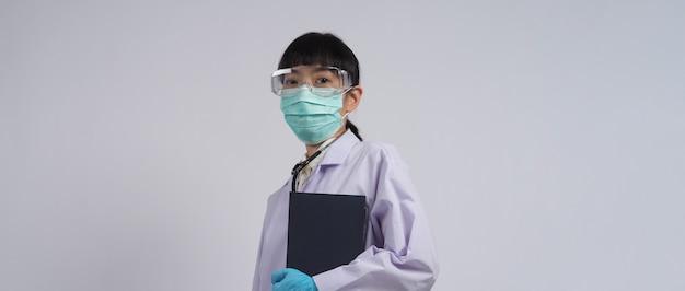 Arzt in uniform zeigt auf einen leeren bereich. tragen von blauen medizinischen latexhandschuhen und einer durchsichtigen schutzbrille und einer grünen n95-maske, um epidemische viren zu verhindern. asiatischer arzt. handbewegung. medizinisches stethoskop. virenbuch
