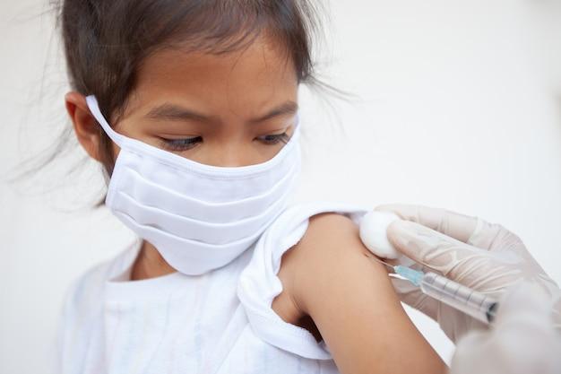 Arzt injiziert impfung auf asiatischen kindermädchenarm und mädchen, die schutzmaske tragen, um virus zu schützen