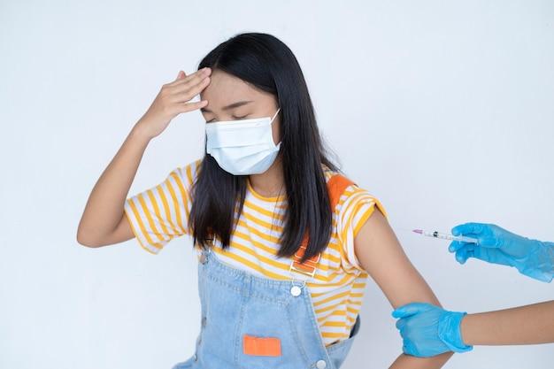 Arzt injiziert impfung in den arm eines jungen asiatischen mädchens auf weißem hintergrund student medizinisches konzept