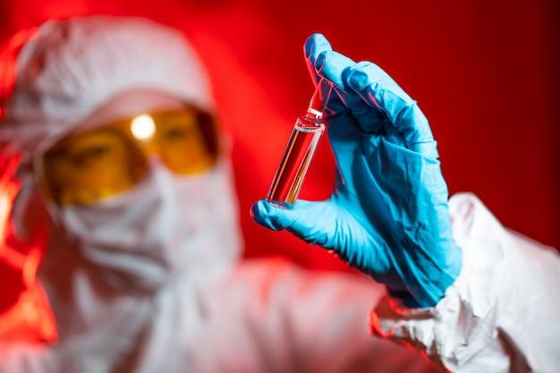 Arzt, krankenschwester, wissenschaftler hand in blauen handschuhen mit grippe, masern, coronavirus, covid-19-impfstoff