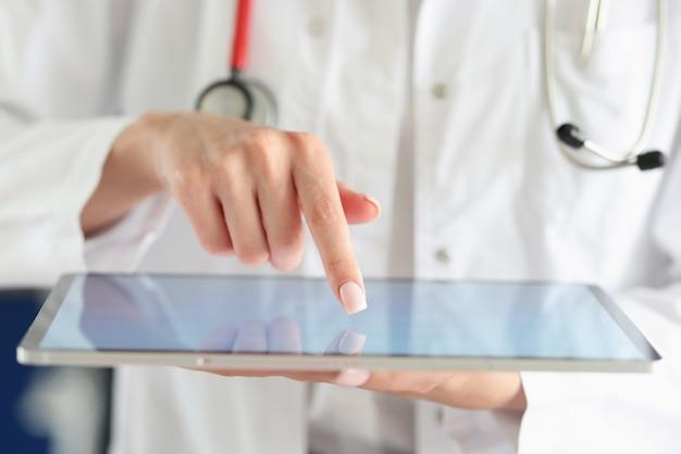 Arzt legt seinen finger auf den touchscreen des digitalen tablets in der kliniknahaufnahme