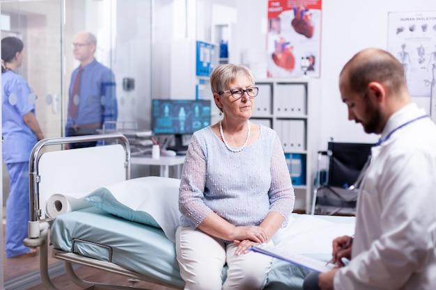 Arzt liest diagnose für kranke ältere frau, die auf krankenhausbett im untersuchungsraum sitzt