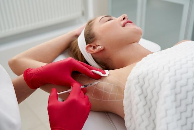 Arzt macht injektionen von botulinumtoxin in den achselbereich gegen hyperhidrose in der schönheit