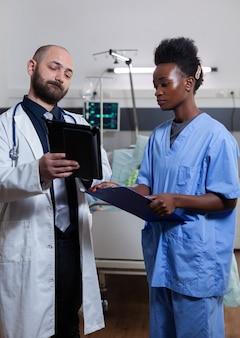 Arzt mit assistent, der die behandlung der krankheitswiederherstellung mit einem tablet-computer während der ärztlichen beratung in der krankenstation überprüft