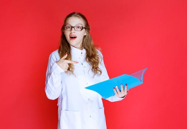 Arzt mit blauem ordner sieht überrascht aus.