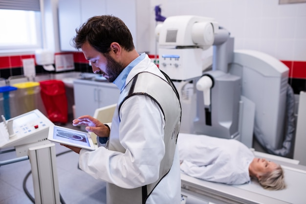 Arzt mit digitaler tablette und patient auf röntgengerät liegend