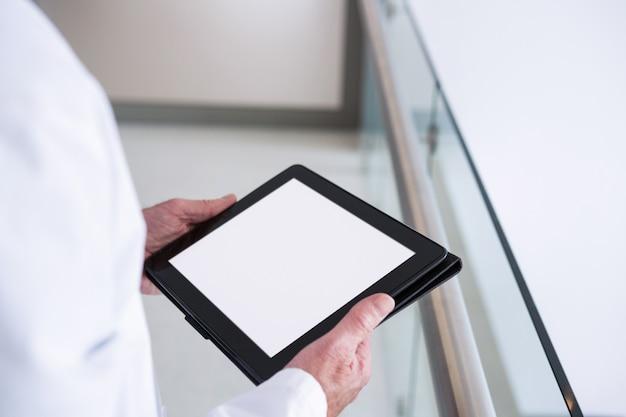 Arzt mit einem digitalen tablet im durchgang im krankenhaus