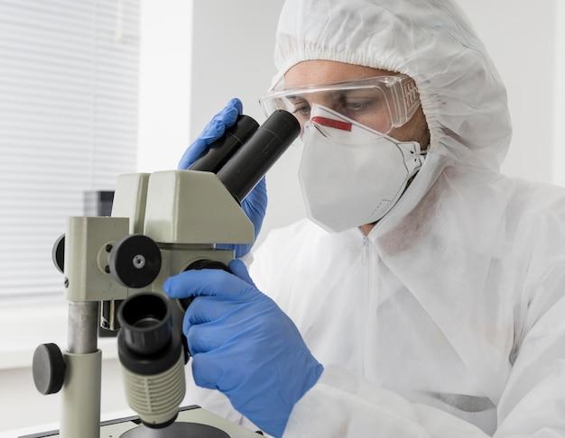 Arzt mit einem mikroskop zur überprüfung der covid-probe