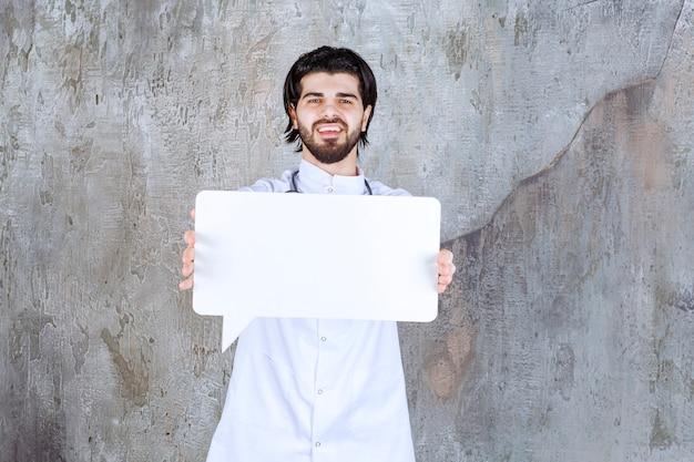 Arzt mit einem stethoskop, das eine leere infotafel in rechteckform hält
