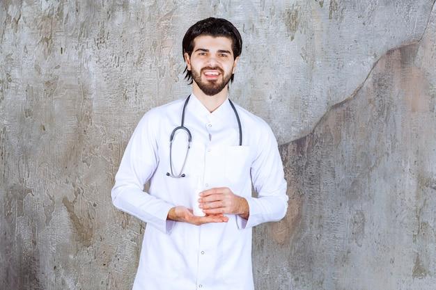 Arzt mit einem stethoskop, das eine weiße tube händedesinfektionsspray hält