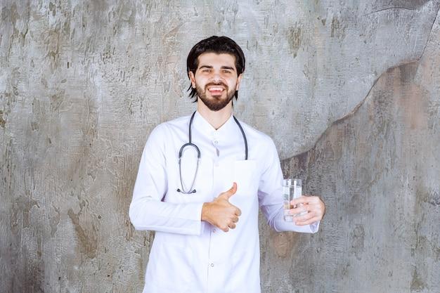 Arzt mit einem stethoskop, der ein glas reines wasser hält und ein positives handzeichen zeigt