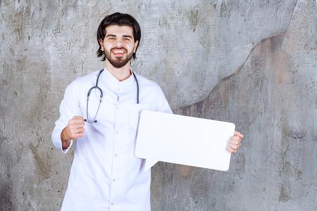 Arzt mit einem stethoskop, der eine leere infotafel in rechteckform hält und seine faust zeigt