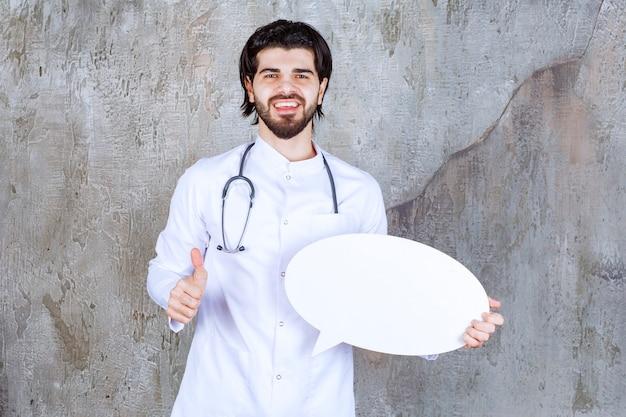 Arzt mit einem stethoskop, der eine ovale leere infotafel hält und ein positives handzeichen zeigt