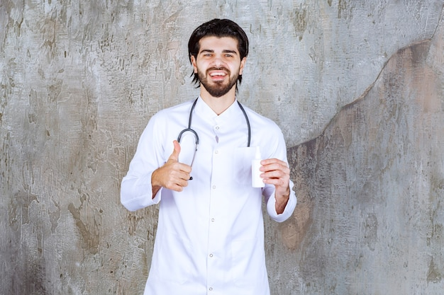 Arzt mit einem stethoskop, der eine weiße tube händedesinfektionsspray hält und daumen hoch zeigt