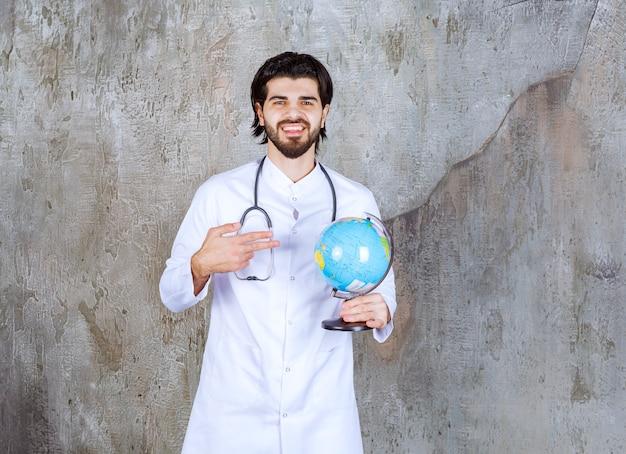 Arzt mit einem stethoskop, der eine weltkugel hält
